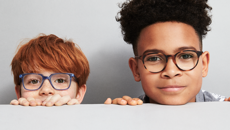 Two children wearing glasses peering over a wall