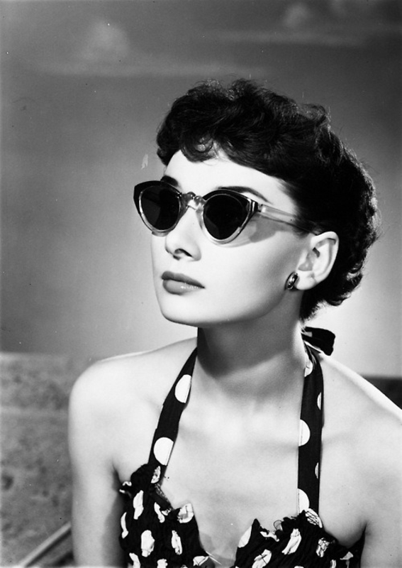 Black and white photo of Audrey Hepburn wearing cat eye glasses
